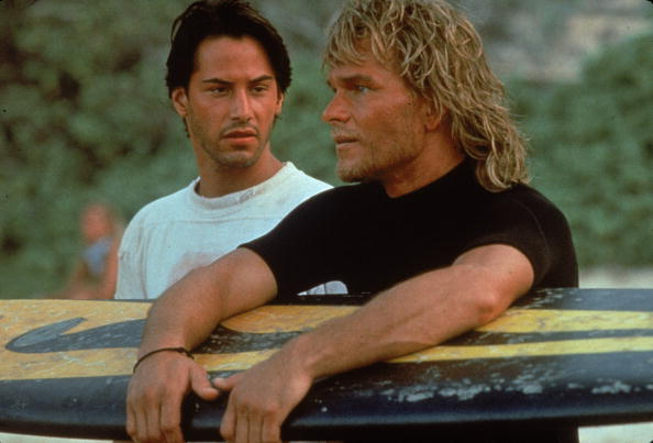 American actor Keanu Reeves and American actor Patrick Swayze stand on a beach as Swayze in'Point Break' (Photo by Richard Foreman/Fotos International/Getty Images)